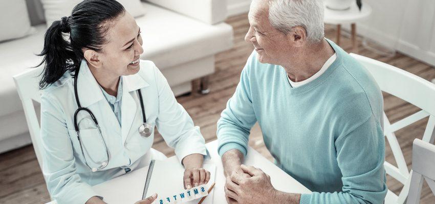 Female nurse explains medication to older man.