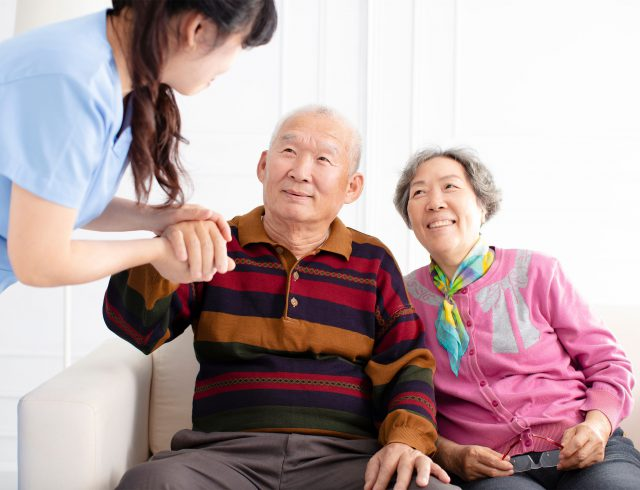 A skilled nurse helps a senior resident of a skilled nursing facility stand up.