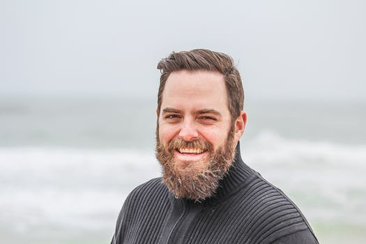 A man with a medium length beard in front of the ocean.