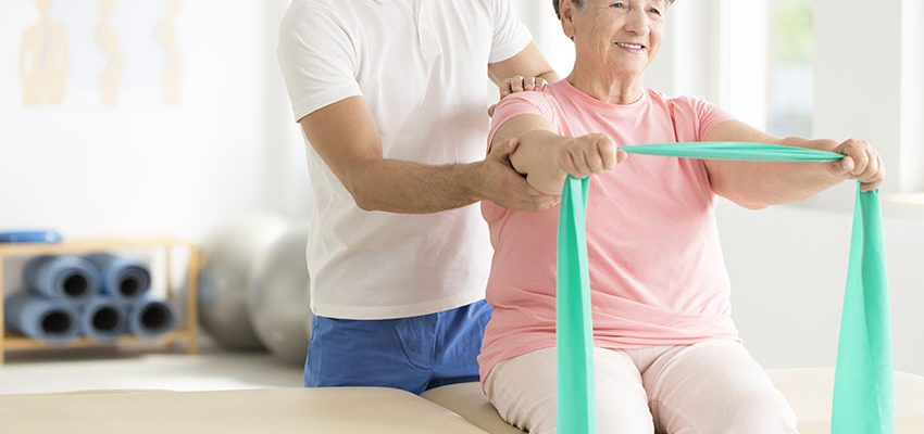 woman holding teal scarf while doing rehabilitation program with physiotherapist