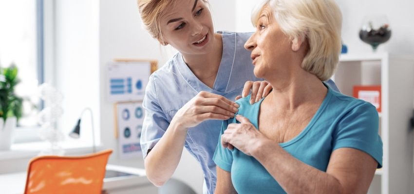 Female nurse helps older female patient.