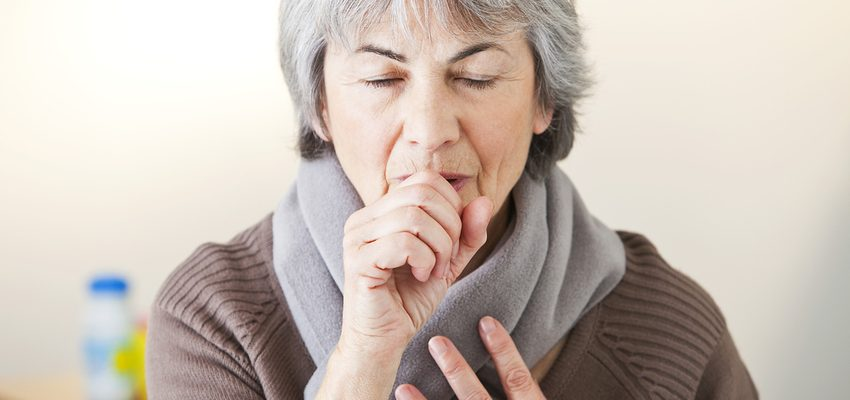 senior woman covering a cough at a Pasadena skilled nursing facility.