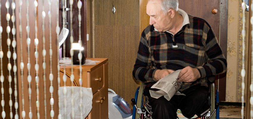 A man in a wheelchair is holding a newspaper in a high-quality Pasadena care facility.