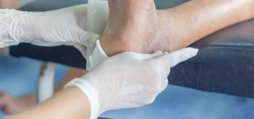 A skilled nursing professional at a Pasadena care facility applies bandages to a senior's foot.