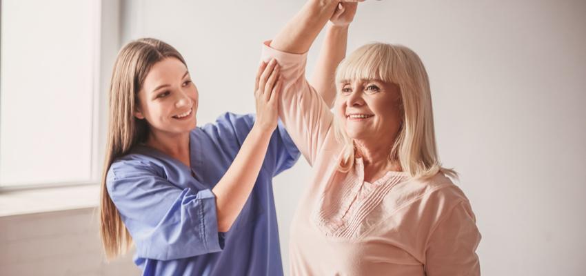 A senior woman and nurse engage in orthopedic rehab.