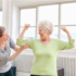 A senior woman engages in physical rehab with a skilled nurse.