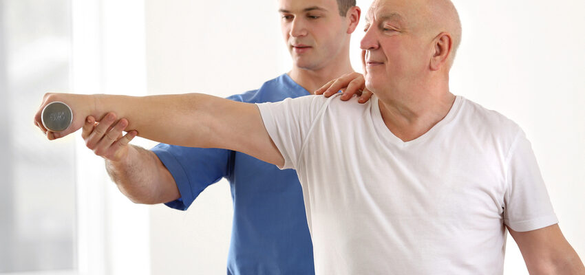 A skilled nursing professional helps a man lift weights as part of physical rehab.